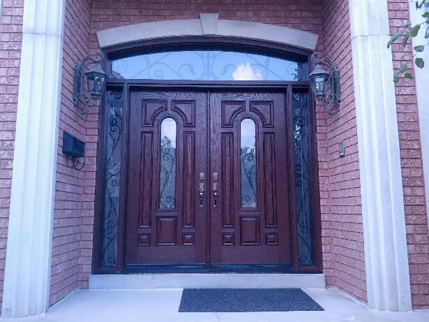 Fiberglass Doors-Fiberglass 8 Panel 8 foot doors with 2 Wrought Iron Design side lites and Transom Installed in Richmond Hill by windowsanddoorstoronto.ca