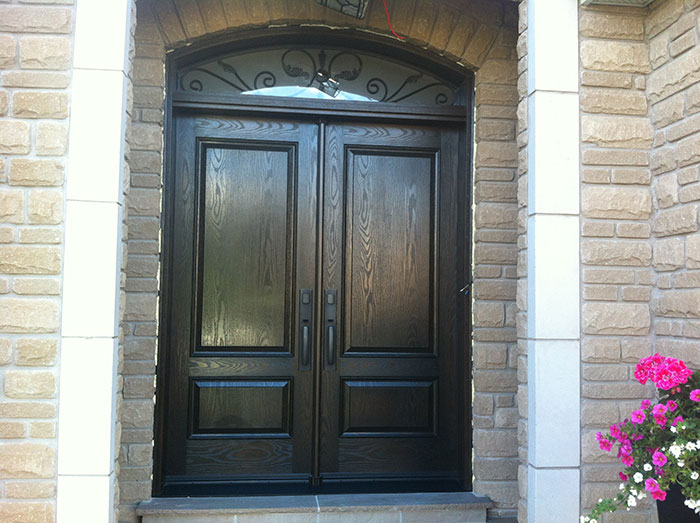 Wood Grain Fiberglass Doors with Iron Art Design Transom by Windows and Doors Toronto Installed in Etobicoke