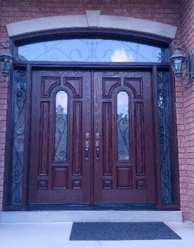 Wrought Iron Fiberglass Doors-Fiberglass 8 Panel 8 foot doors with 2 Wrought Iron Design side lites and Transom Installed in Richmond Hill by windowsanddoorstoronto.ca